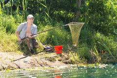 Fisherman using a net to land a fish. Elderly disabled fisherman with one leg using a net to land a fish as he sits on the ground at the edge of a lake royalty free stock image