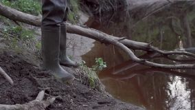 A fisherman in waders. Stands on the shore of a small river stream stock footage