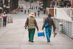 Fisherman walking with cooler after fishing on the Hermosa Beach pier in California. Two men dressed for fishing and with their fishing poles, walk with a cooler stock photos