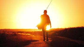 Fisherman walking at sunset sky background. The man is holding a fishing rod and tackle. Go off into the distance at. Sunset, concept, lifestyle stock video footage