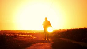 Fisherman walking at sunset sky background. The man is holding a fishing rod and tackle. Go off into the distance at. Sunset, concept, lifestyle stock video