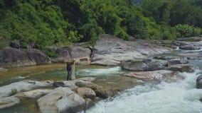 Fisherman Walks on River Rocks with Net against Foamy Rapids stock video footage