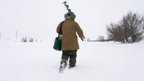 A fisherman walks on a snow-covered lake in search of a good fishing place. Royalty Free Stock Image