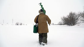 A fisherman walks on a snow-covered lake in search of a good fishing place. Stock Photo