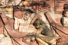 Fisherman wall art carved sculpture. On the blocks of rock royalty free stock images