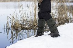 Fisherman in warm shoes stands near a river in the snow. Fisherman in warm shoes stands near river on snow concept of fishing Stock Image