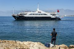 A fisherman watches a cruise ship move through Antalya Bay in Turkey. Royalty Free Stock Photography