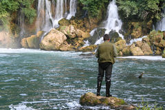 Fisherman and the waterfalls. Man fishing on a lake with waterfalls royalty free stock photo
