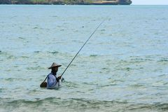Fisherman in the waves of ocean. Travel around Indonesia. Nature of Asia. stock photo
