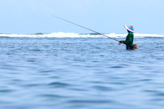 Fisherman. Wearing headcovering standing in the ocean to catch some fish in Indonesia Stock Photos