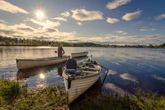 Fisherman on White Wooden Boat Royalty Free Stock Photography