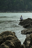 Fisherman who is fishing on the rocks Royalty Free Stock Photo