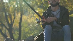 Fisherman winding line waiting for big biting, fishing, real men activity. Stock footage stock video footage