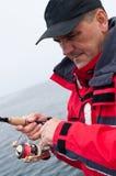 Fisherman winding reel stock photo