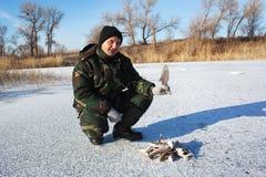 Fisherman on winter lake Stock Images