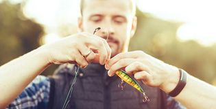 Free Fisherman With A Spinning And Bait Catching Fish On A Lake Or River. Man On A Weekend With A Fishing Road. Hobby And Royalty Free Stock Image - 141619966