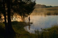 A fisherman on a wooded lake in the fog royalty free stock photography