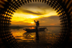 Fisherman on wooden boat casting a net for catching fish in morn Royalty Free Stock Images