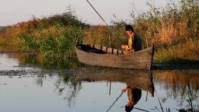 Fisherman in a wooden boat stock video