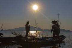 Fisherman on a wooden boat with sunset background. Two fisherman stand on vintage wooden boat with sunset and mountain background Stock Photos