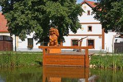 Fisherman wooden figure over the pond. Fisherman holding fish in his hands wooden figure over the pond stock photo
