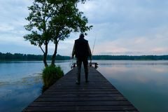 Fisherman. On wooden pier during cloudy day Royalty Free Stock Images