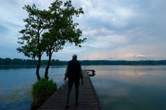 Fisherman. On wooden pier during cloudy day Stock Image