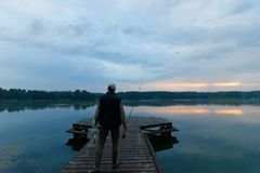 Fisherman. On wooden pier during cloudy day Royalty Free Stock Photos