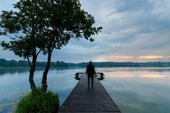Fisherman. On wooden pier during cloudy day Royalty Free Stock Image