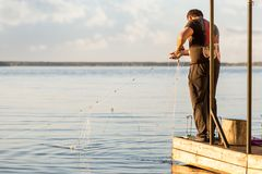 Fisherman on wooden pierce. Fishing man taking out net from water. Sunset time. Copyspace royalty free stock photography