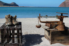 Fisherman Work Boots and Scale on Beach Espiritu Santo Island Mexico. Work items such as boots and a fishing scale on the beach of a fisherman's camp on the Royalty Free Stock Images