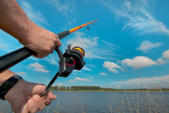 Fisherman at work with a casting rod Stock Photography
