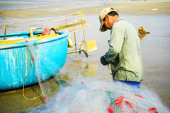 Fisherman working on the beach Royalty Free Stock Photos