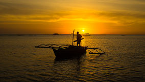 Fisherman working on his boat at Sunset Stock Photography