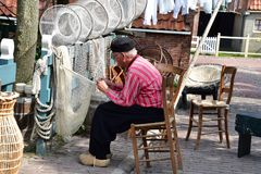 Fisherman working at his fishnet. Dutch fisherman sitting on the chair and working at his fishnet Stock Photography
