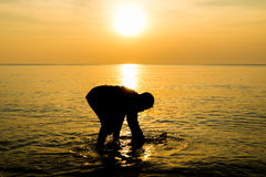 Fisherman working in sunrise at beach. Royalty Free Stock Image