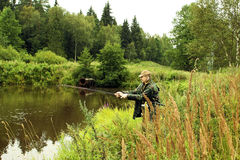Fisherman. A young man fisherman catches fish in the summer at the shore of the pond in the summer stock photo