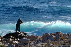 Fishermann. In sea Mediterranée with big waves Royalty Free Stock Photos