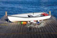 Fishermans boat. On wooden deck near water Royalty Free Stock Image