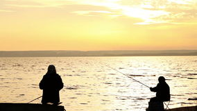 Fishermans on the calm sunset seaside Royalty Free Stock Photography