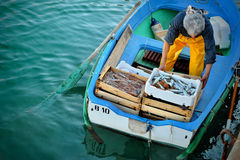 Fishermans with a catch in port unload their ashore. Stock Photo