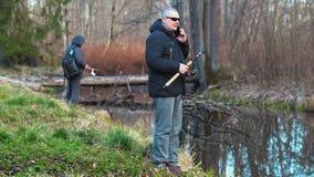Fishermans con las cañas de pescar y el teléfono elegante en el banco de río metrajes