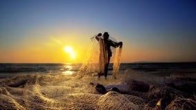 Fishermans de coucher du soleil tirant les poissons contagieux nets sur l'océan Images stock