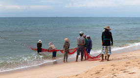 Fishermans dragging fishing nets Stock Images