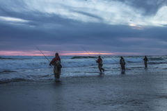 Fishermans fishing on the ocean sunset Royalty Free Stock Image