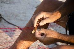 Fishermans-` Hände, die Fischernetz reparieren Stockbilder