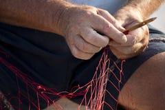 Fishermans-` Hände, die rotes Fischernetz reparieren Lizenzfreie Stockfotos