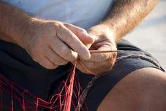 Fishermans-` Hände, die rotes Fischernetz reparieren Stockbilder
