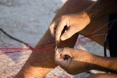 Fishermans` handen die rood visnet herstellen royalty-vrije stock afbeelding