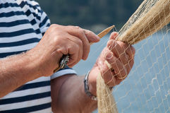 Fishermans hands. Fisherman knits a fishing net in Rovinj, Croatia Royalty Free Stock Photo